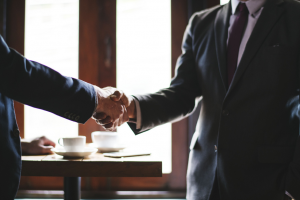 Two business people in a suit and tie shaking hands. Convertibill Blog